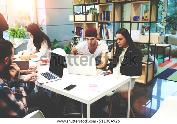 Group of students working together at laptop computer in a university library. Team of copywriters with net-book creating a text for a new release in the wording. Freelancer using wireless devices