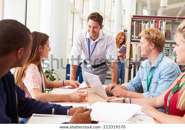 Group Of Students Working Together In Library With Teacher