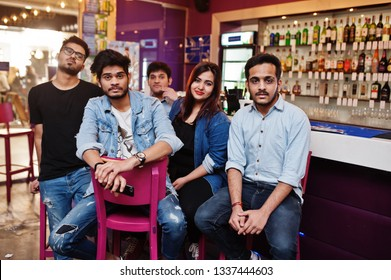 Group of stylish asian friends wear on jeans sitting at chairs against bar in club.