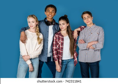 group of stylish teenagers standing together isolated on blue