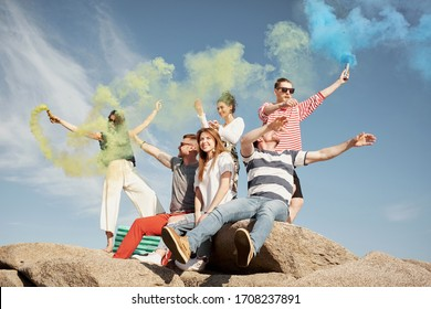 Group of stylish young people sitting on rocks with smoke grenades and enjoying beautiful summer day, low angle view