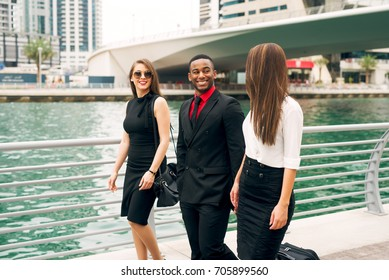 Group of stylish young people walking near the river.