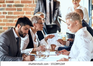 Group of stylishly dressed businessmen sit at table in office and discuss new project. Focused blond caucasian woman who speaks