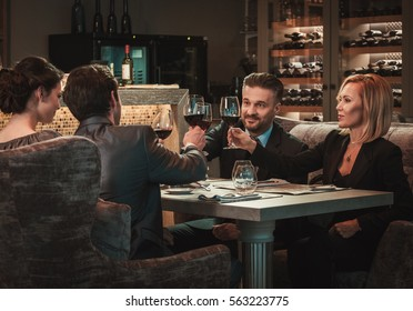 Group of successful business people clinking glasses of red wine during business dinner in restaurant