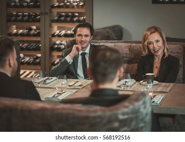 Group of successful business people discussing during business dinner in restaurant.