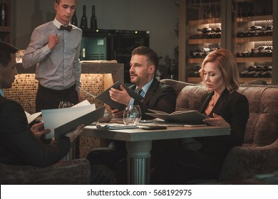Group of successful business people with menu in restaurant.
