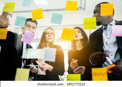 Group of successful business teamwork. Brainstorm meeting with colorful sticky paper note on glass wall for new ideas. Using agile methodology and do business. Brainstorming in a tech start-up office.