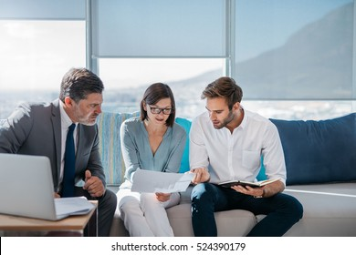 Group of successful businesspeople discussing paperwork and using a laptop together while sitting on a sofa in a modern office