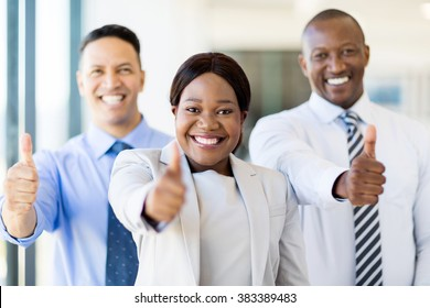 group of successful businesspeople giving thumbs up