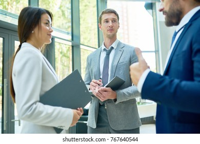 Group of successful businesspeople holding clipboards standing in hall of modern office building discussing work with boss, focus on smiling Asian businesswoman