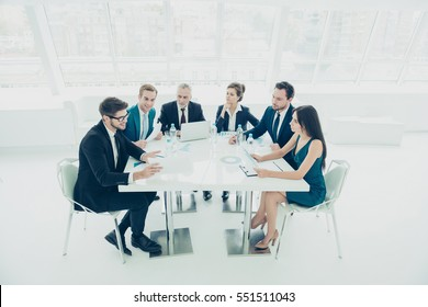 Group of successful businesspeople talking together while working around  table in office