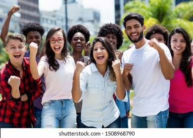 Group of successful cheering latin and caucasian and hispanic and african american young adults outdoor in summer in city
