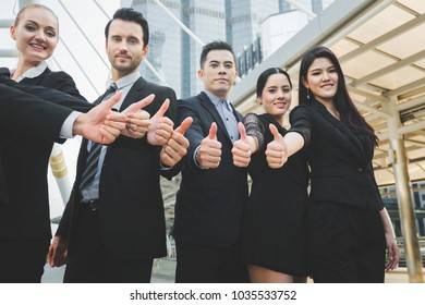 Group of successful professional business team with thumbs up outdoor with office building background