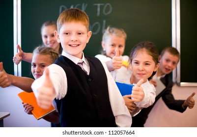 Group of successful schoolchildren showing thumb up together in the classroom