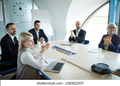Group of successful speakers applauding to one of them while sitting by round table in boardroom