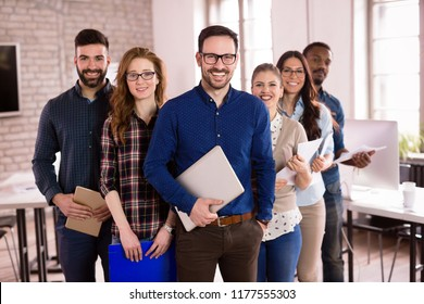 Group of successful young architects posing in office