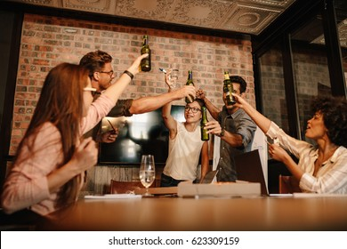 Group of successful young business professionals celebrating with beers. Diverse group of people having drinks over successful business deal.