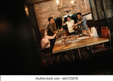 Group of successful young business professionals celebrating in office conference room. Diverse business team having food and drinks at start up office.