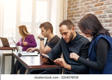 Group of successful young men and women working together in the office. Team of programmers looking for creative decision directing by female team leader.