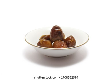 A group of sukkari dates (kurma sukari) on a small plates isolated on white background, perfect for breakfasting during ramadan