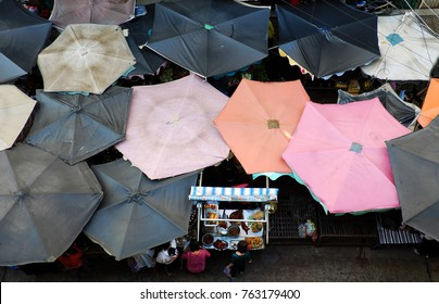 Group of sunshade from top view at outdoor farmers market, Ho Chi Minh city, Vietnam, woman at roast duck pushcart, amazing food counter from high view at morning