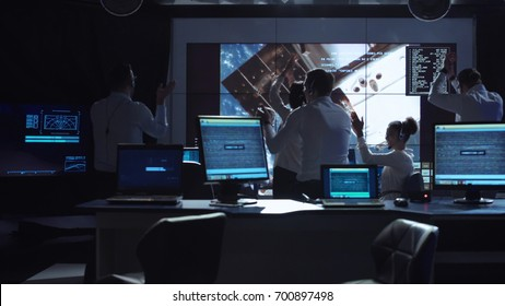 Group of supervisors celebrating docking of spaceship in dark room of mission control center. Elements of this image furnished by NASA.