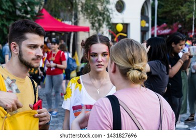 Group of supporters of sexual diversity in bright colors clothing and makeup having a conversation  during Pride Parade. Bucharest, Romania, June 22, 2019.