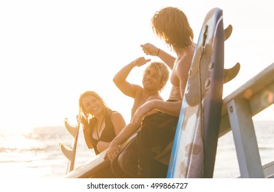 Group of surfers chilling out on the beach. sitting on the lifeguard house and having fun
