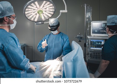 Group of surgeons using augmented reality holographic hololens glasses while operating in modern operation theater