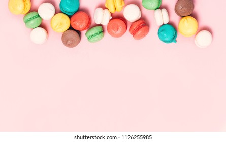 Group of sweet colorful mini macarons on soft pink paper background with copy space for adding text. Top view, flat lay.
