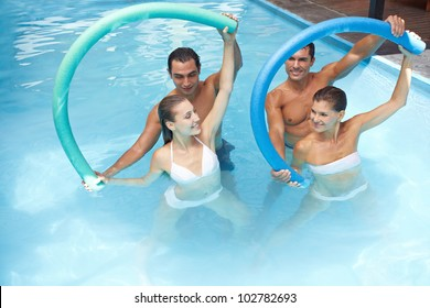 Group in swimming pool doing water aerobics with swim noodles