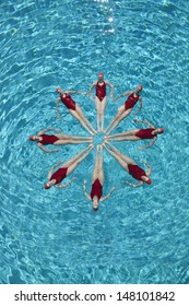 Group of synchronised swimmers forming a circle in pool