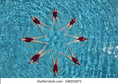 Group of synchronised swimmers forming a star shape in pool