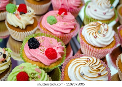 group of tasty cupcakes on a white wooden table