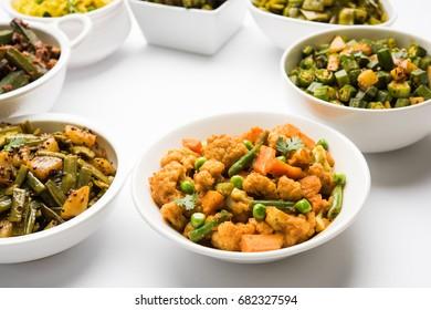 Group of Tawa fry sabzi or sabji like cauliflower/Phool Gobhi, bhindi OR okra, Gwar OR Cluster Beans, French Beans, Cabbage or Patta Gobi, Flat Green Beans, served in a bowl. selective focus