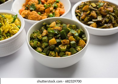Group of Tawa fry sabzi or sabji like cauliflower/Phool Gobhi, bhindi OR okra, Gwar OR Cluster Beans, French Beans, Cabbage or Patta Gobi, Flat Green Beans, served in a bowl. selective focus