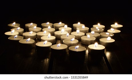 A group of tealights, candlelight in the dark, Focus is in the foreground