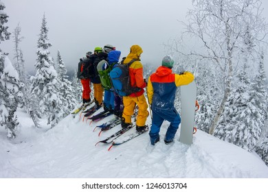 Group team of free-riders skiers, snowboarders stand on the mountainside and look down