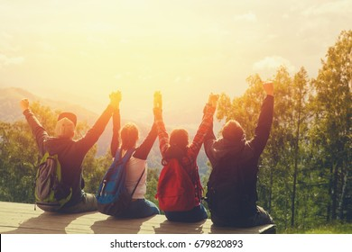 Group of team of friends sitting on top of a mountain, holding hands and rejoice, watching leaving sun behind the mountains - sunset.