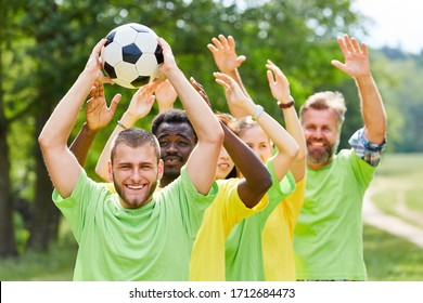 Group as a team plays with football at a teambuilding event