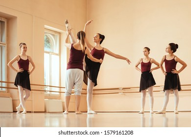 Group of teenage ballerinas having a class at ballet studio. Ballet teacher is assisting to one of them.
