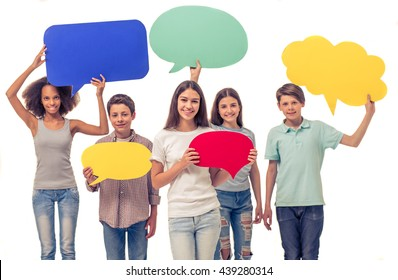 Group of teenage boys and girls is holding speech bubbles, looking at camera and smiling, isolated on white