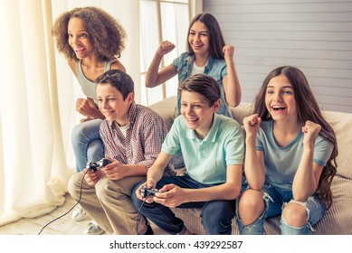 Group of teenage boys and girls is playing game console and smiling while sitting on the couch at home