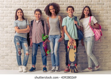 Group of teenage boys and girls with school backpacks and skateboards is looking at camera and smiling, standing against white brick wall
