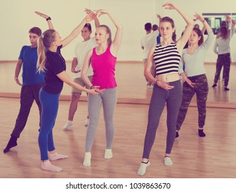 Group of teenage boys and girls studying ballet dance in dance hall