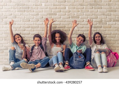 Group of teenage boys and girls is using gadgets, keeping hands up, looking at camera and smiling, sitting against white brick wall