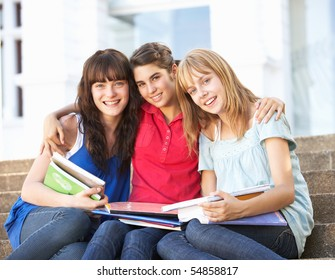 Group Of Teenage Female Friends Sitting On College Steps Outside