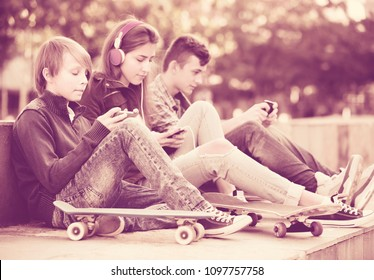 Group of teenage friends in casual relaxing with mobile phones outdoor