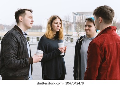 group of teenage friends having a conversation while standing together on city street holding coffee cups