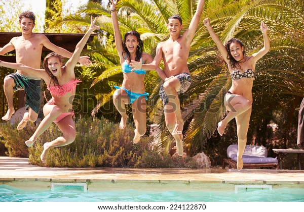 Group Of Teenage Friends Jumping Into Swimming Pool